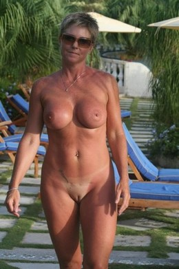Mature woman posing nude on the beach:..